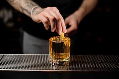 Bartender adds lemon zest in alcohol cocktail. Male tattooed bartender adds fresh lemon zest in cold alcohol cocktail with whiskey stock photo
