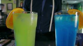 Bartender adorns two cocktails of orange slices. Dolly shot stock video