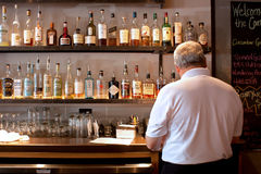 Bartender at the Bar. A bartender goes about his business at his bar royalty free stock photography