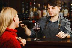 Bartender at bar counter pours red wine in glass. Bartender in apron at bar counter pours red wine from bottle in glass for blond girl that sits on other side stock photos