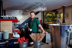 Bartender barista with coffee in hand behind the bar at the brea royalty free stock photos
