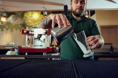 The bartender barista pours hot milk into a glass in bar cafe royalty free stock photo