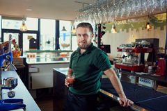 The bartender barista waiter with a glass of fresh juice is rest royalty free stock photo