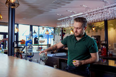 The bartender with beard behind bar pours a drink into glass stock photo