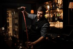 Bartender with a beard making cocktail in the steel shaker. On the bar counter in the blurred background of the bar shelves stock photo
