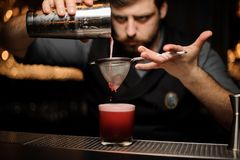 Bartender with a beard pouring a smooth red cocktail through the sieve to the glass with one big ice cube. On the bar counter on the blurred background royalty free stock photo