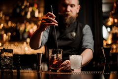 Bartender with a beard stirring alcohol with an ice cubes in the tall measuring glass cup with a spoon. On the bar counter on the blurred background stock images