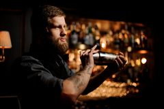 Bartender with a beard and tattoo on hands holding a steel shaker. On the bar counter in the blurred background of the bar shelves stock image