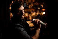 Bartender with a beard and tattoo on hands holding a steel shaker and looking at camera. In the blurred background of the bar shelves stock photo
