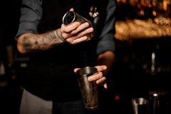 Bartender with a beard and tattoo on hands making cocktail in the steel shaker. On the bar counter in the blurred background of the bar shelves stock photography