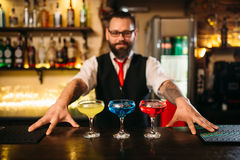 Bartender behind bar counter show alcohol coctails Stock Image