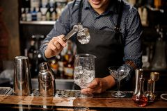 Bartender holds the piece of ice by tweezers. Bartender in black apron and blue shirt holds the piece of ice by tweezers at a bar counter Stock Photo