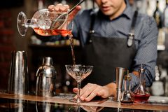 Bartender pours sweet cocktail in bocal Stock Photos