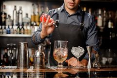 Bartender pours syrup in cocktail glass with ice Royalty Free Stock Photography
