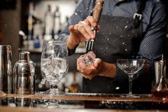 Bartender splitting a piece of ice at a bar counter. Bartender in black apron and blue shirt splitting pieces of ice by little piolet at a bar counter Royalty Free Stock Photos