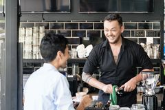 Bartender cleaning the espresso machine while talking with a cus Royalty Free Stock Image