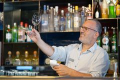 The bartender wipes out the wine glass at work. The bartender cleans the glass. A handsome bartender polishes a glass of wine glasses. The concept of service Royalty Free Stock Images