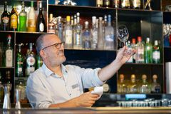 The bartender wipes out the wine glass at work. The bartender cleans the glass. A handsome bartender polishes a glass of wine glasses. The concept of service Royalty Free Stock Image