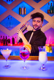 Bartender with cocktail shaker at bar counter. Handsome bartender with cocktail shaker at illuminated bar counter royalty free stock photo