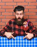 Bartender concept. Man in checkered shirt on brick wall background. Barman with long beard and mustache and stylish hair. On shocked face , made alcoholic Royalty Free Stock Photography