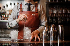 Bartender cooling out Cocktail glass mixing ice with a spoon. No face Stock Photos