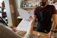 Bartender and customer menu at bar. Small business, people and service concept - bartender and customer menu at bar or coffee shop Stock Photos