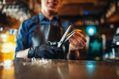 Bartender cut rind from oranges at the bar counter. Male bartender in apron cut rind from oranges at the bar counter. Alcohol beverage preparation. Barman royalty free stock images