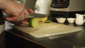 Bartender Cutting en limefrukt i ett kafé lager videofilmer