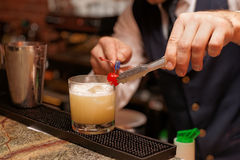 Bartender is decorating cocktail with cherry Stock Images