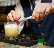 Bartender is decorating cocktail with cherry Royalty Free Stock Images