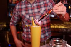 Bartender is decorating a cocktail with mango Royalty Free Stock Photo