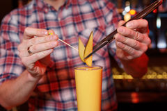 Bartender is decorating a cocktail with mango Royalty Free Stock Images
