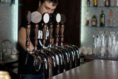 Bartender dispensing draught beer royalty free stock images