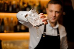 Bartender pouring water from a glass with ice cubes stock images