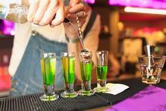 Bartender`en s räcker hällande absint in i en av buntarna som står på räknaren Royaltyfria Foton