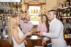 Bartender entertaining guests. Happy bartender entertaining guests at a bar counter Stock Image