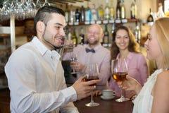 Bartender entertaining guests. Happy bartender entertaining guests at bar counter in bar Stock Photography