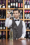 Bartender Examining White Wine In Glass At Shop Counter Royalty Free Stock Image