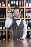 Bartender Examining White Wine In Glass At Shop. Young bartender examining white wine in glass at shop royalty free stock image