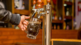 Bartender filling up with craft beer a pint glass royalty free stock photo