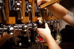 Bartender filling up a dark beer in a glass royalty free stock photography