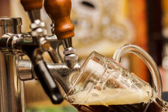 Bartender filling up a dark with craft beer a pint glass stock image