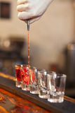 Bartender fills a few glasses in a row Royalty Free Stock Photography