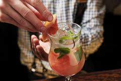 Bartender finished decorating his cocktail with mint and orange slice royalty free stock image