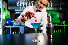 Bartender garnishing cocktail with cherry. On bar counter in bar Royalty Free Stock Images
