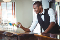 Bartender garnishing cocktail with olive Royalty Free Stock Photography