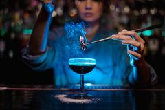Bartender girl adding to a brown cocktail a flamed badian with tweezers in the blue light. Bartender girl adding to a brown cocktail a flamed badian with stock image