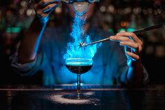 Bartender girl adding to a brown cocktail and pour on a flamed badian on tweezers a powdered sugar in the blue light. Bartender girl adding to a brown cocktail stock photos