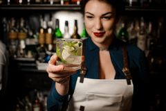 Bartender girl holding an fresh cocktail with lime and mint. Bartender girl holding a fresh delicious summer cocktail with the lime and mint in the glass in the stock photography