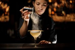 Bartender girl holding a steel spice shaker adding to a delicious cocktail flavours. On the bar counter in the blurred background stock photo